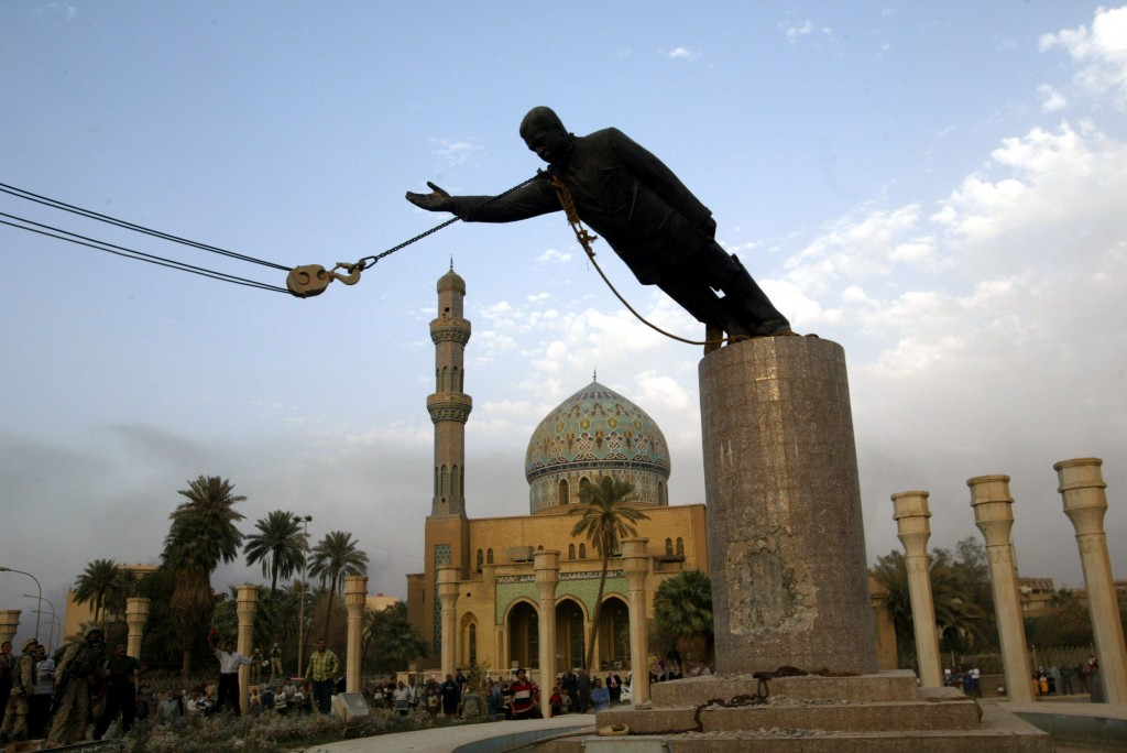 A statue of Iraq's President Saddam Hussein falls as it is pulled down in central Baghdad April 9, 2..